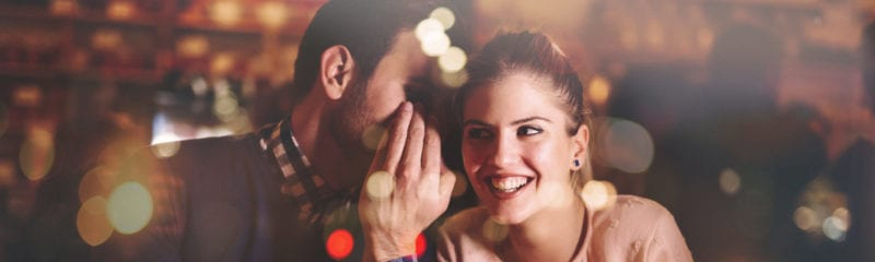 dating while separated; man whispering into young woman's ear while she smiles