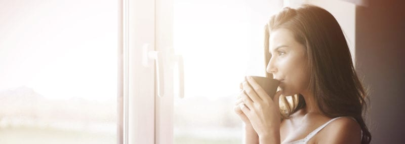 woman drinking coffee and staring out window