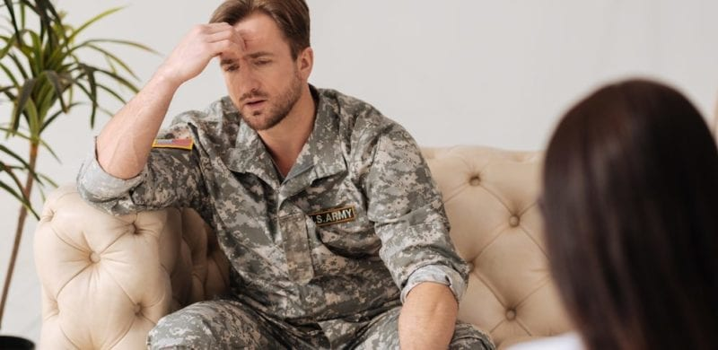 military man looking frustrated sitting on couch talking to woman; military divorce