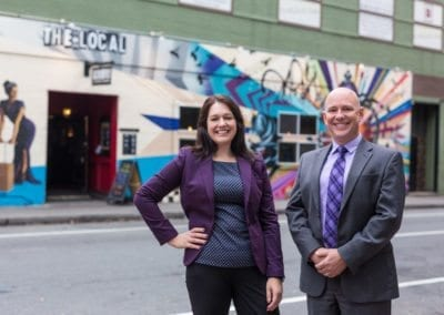 Angela and Sean McIlveen in front of painted wall